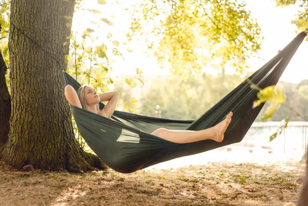Young woman relaxing in hammock by the lake - GUSF02297
