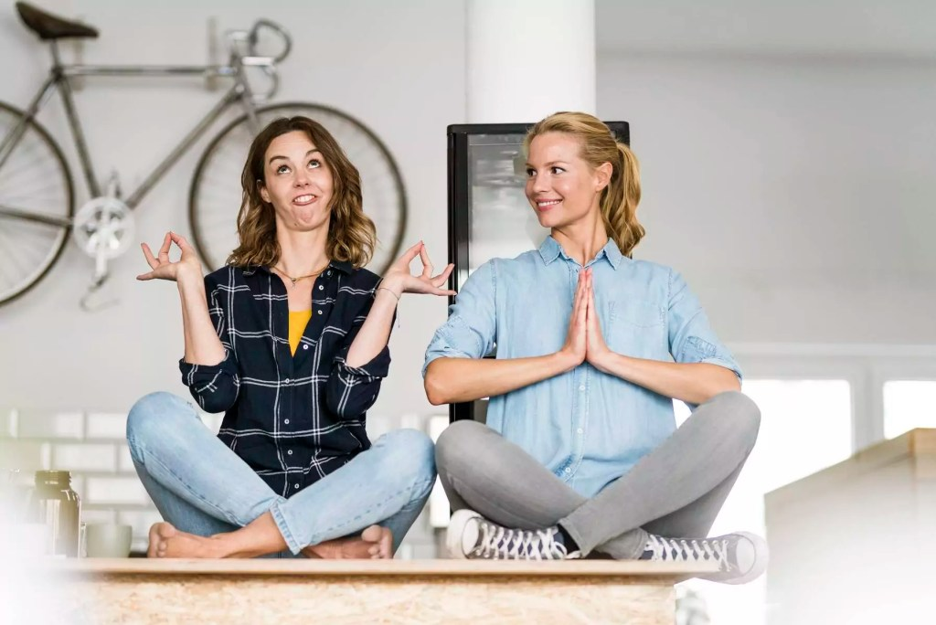 Two young women sitting cross-legged on the counter of their coffee shop, one meditating , other pulling funny faces - JOSF03435