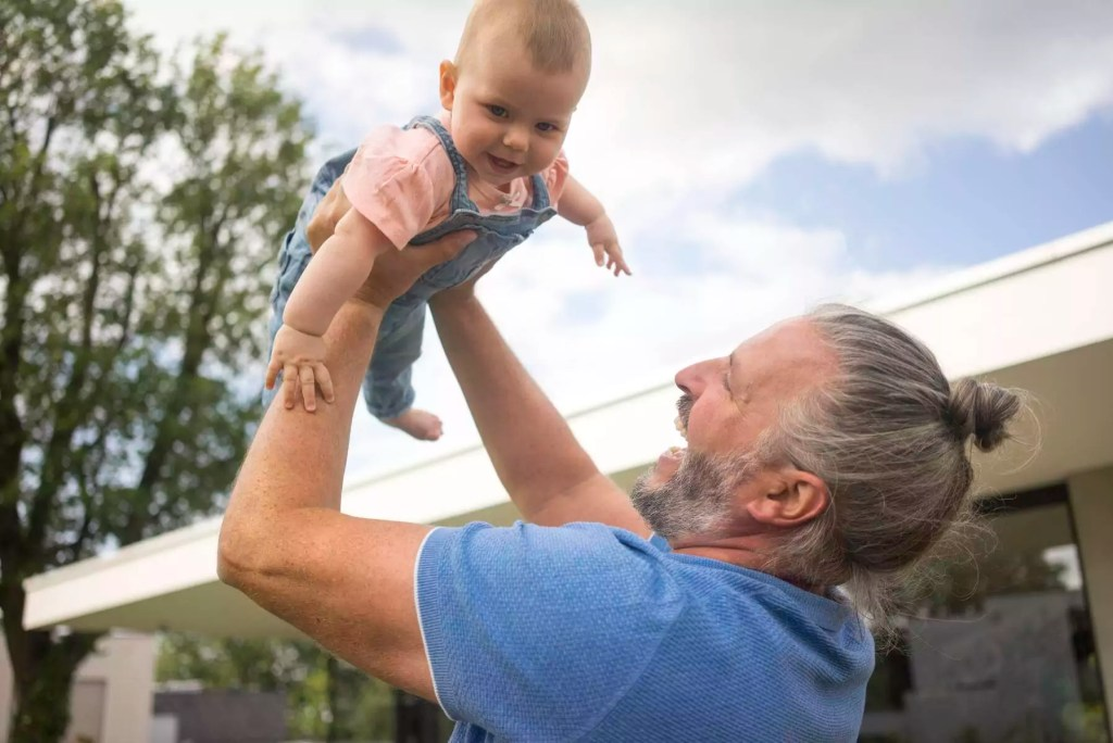 Happy mature man lifting up baby girl in garden of his house - MOEF02434