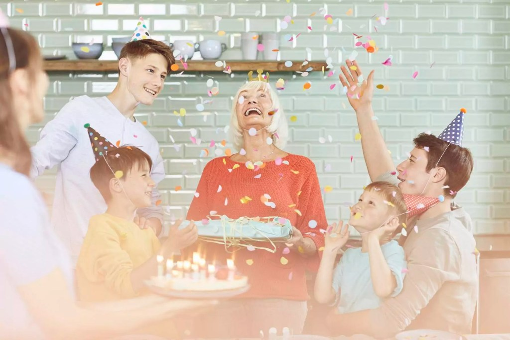 Mother and sons celebrating grandmother's bithday in their kitchen - MCF00207