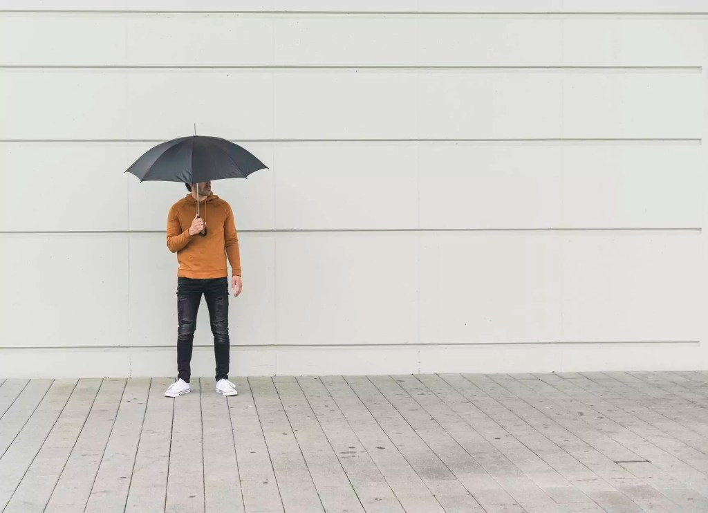 Young man with umbrella standing in the street - UUF17885