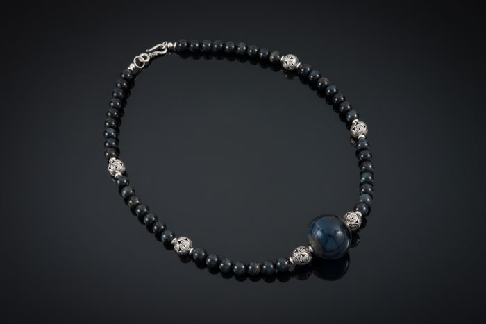"""Becky Congdon """"Jazz Necklace"""" 20.5"""" handmade flameworked glass hollow bead with blue tigers eye gemstone beads and sterling silver (photo by Ann Cady) $180."""
