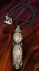 """San Fortune """"Lace Agate Pendant"""" (view C) Mexican Crazy Lace Agate and Laguna Lace Agate surrounded by glass seed bead bezels, 2 glass flowers, 4 bronze spirals and various size glass beads (pendant 5.5""""x1.5"""") 16.5"""" handmade chenille stitched rope w/ beaded toggle closure $324."""