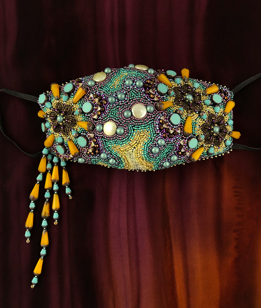 """San Fortune """"Happiness Can Make It Through"""" View A face mask made of fabric, 3 filigree metal flowers, coin freshwater pearls, glass drops, glass discs, glass triangle beads, glass dome beads and various other glass beads $435. SOLD"""