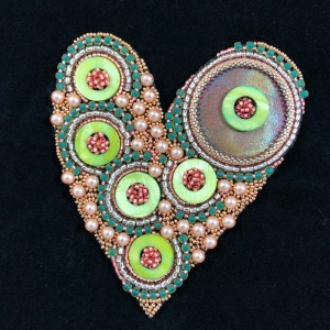 "San Fortune ""Love"" 5.5x4.5 bead embroidery on framed black panel raku focal, Swarovski pearls, dyed shell rings, glass see beads $275. SOLD"