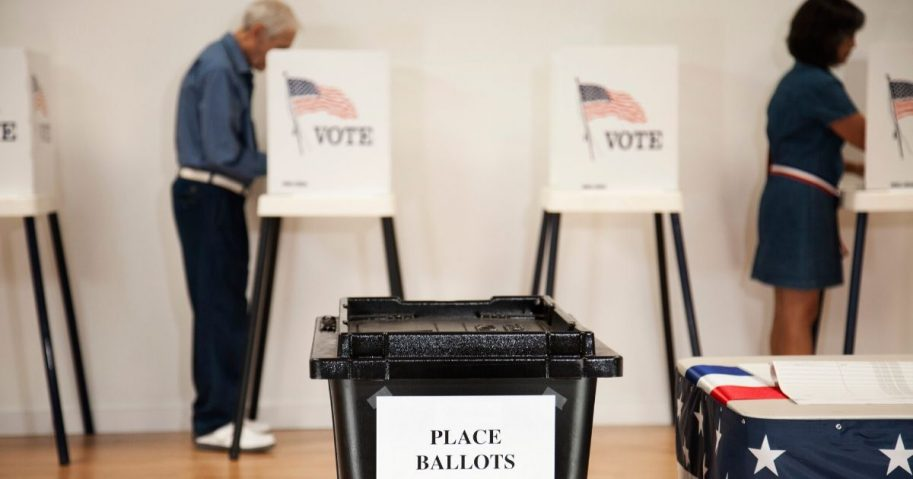 Stock image of a ballot box with voters in the background.