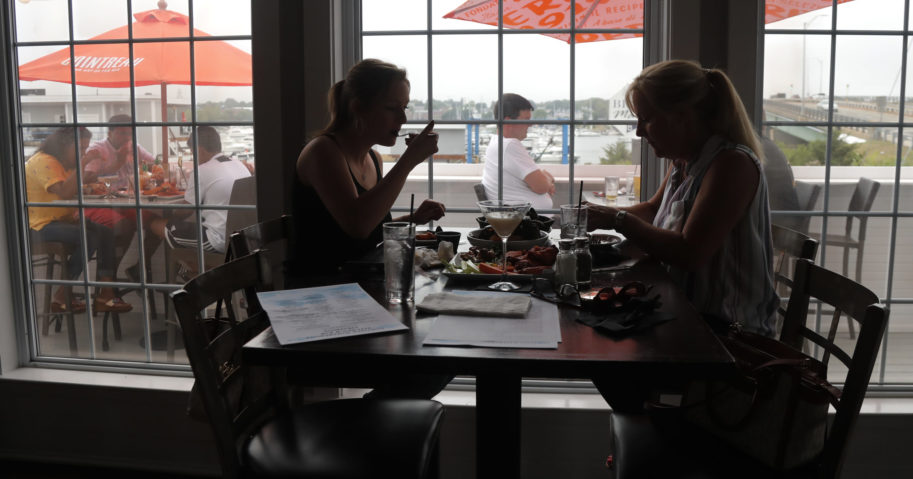 In this June 22, 2020, file photo, two women eat lunch at Portside Restaurant in Salisbury, Massachusetts, after state guidelines allowed for indoor dining. A new poll from The Associated Press-NORC Center for Public Affairs Research shows Americans becoming less concerned about infection and less supportive of restrictions.