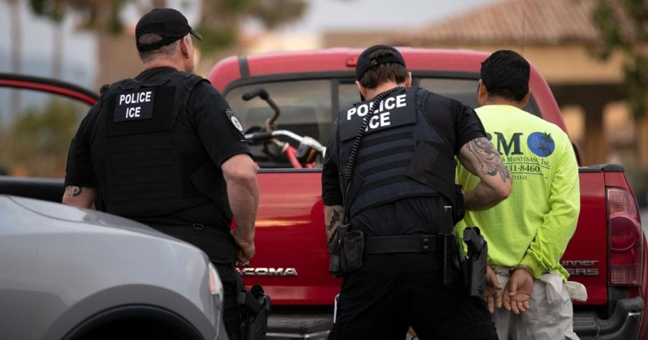 In this July 8, 2019, photo, a U.S. Immigration and Customs Enforcement officers detain a man during an operation in Escondido, California.