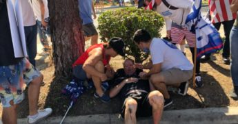 Fellow demonstrators tend to a man injured Saturday when a vehicle drove into a crowd of supporters of President Donald Trump in Yorba Linda, California.