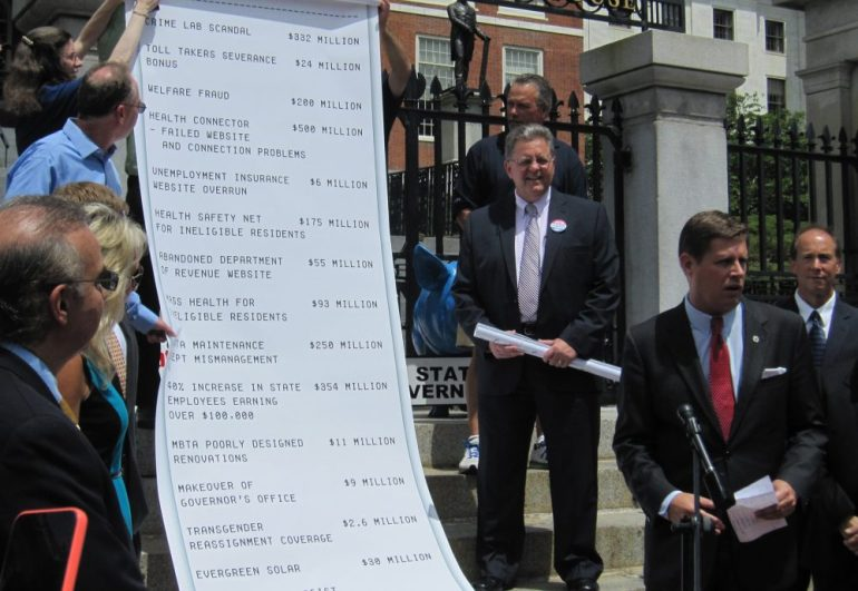 Dennis Galvin (center, with glasses) along a list of government expenditures