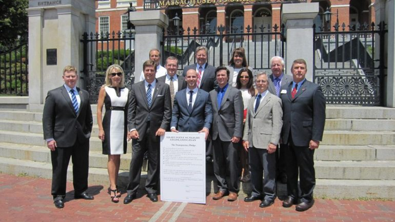 Several people, including Galvin (top center with red tie and glasses) with the pledge at the State House.