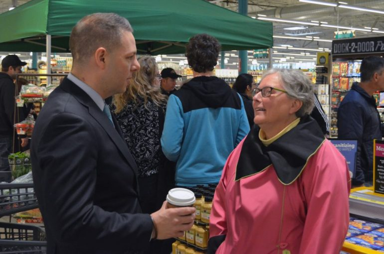 State Representative James Arciero talks with Emily Teller during a very busy early morning at Whole Foods.