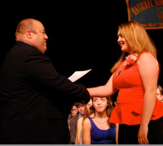 Katlyn Palmer, a sophomore from Westford, receives her National Honor Society certificate from Assistant Principal Matthew Ricard during Nashoba Tech's recent induction ceremony in the Performing Arts Center. (courtesy -Dan Phelps)