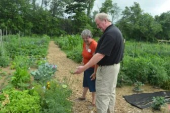 Patti Mason and Chip Barrett look at a flower in the garden.