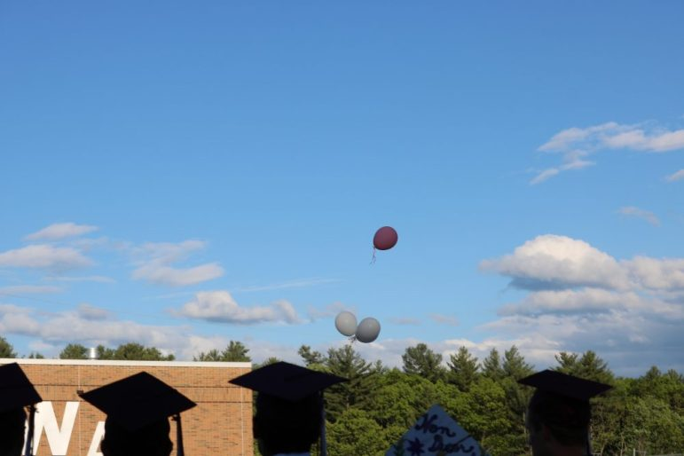 Three white balloons and one pink are released to the sky in memory of the late Erika Gould who would have graduated with the Class of 2017. Gould died at age 7 of a brain tumor. PHOTO BY JOYCE PELLINO CRANE