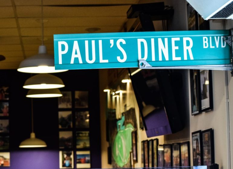 "A sign reading 'Paul's Diner Blvd"" hangs from the entrance of Paul's Diner"