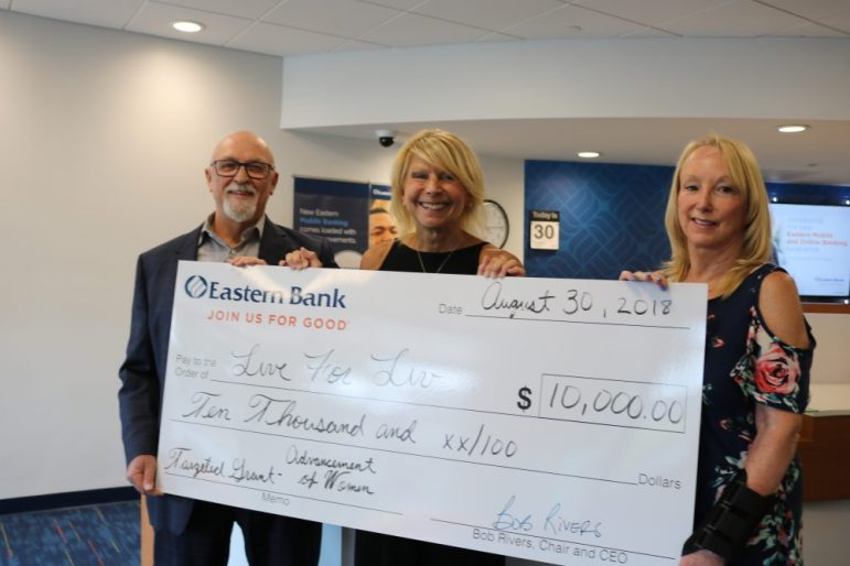 Paul Playe, Jody Marchand, and Carol Aguiar display the grant amount awarded to the Live for Liv Foundation by Eastern Bank. PHOTO BY JOYCE PELLINO CRANE