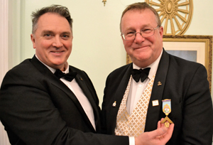 Alan Ball (left) presents Ian Turner with a past master's jewel.