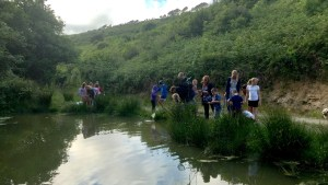 Children and adults taking part in pond dipping on the walks of Kilkhampton Common Cornwall with Westland Countryside Stewards