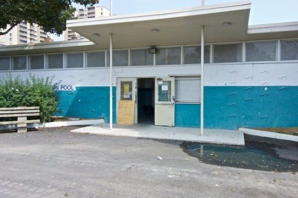 The snack bar has a window at the right of the pool entrance.
