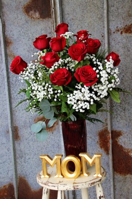 Ruby glass vase filled with 12 long stemmed, premium red roses, baby's breath and lush foliage. Nothing says love more than these amazing roses ! $65.00