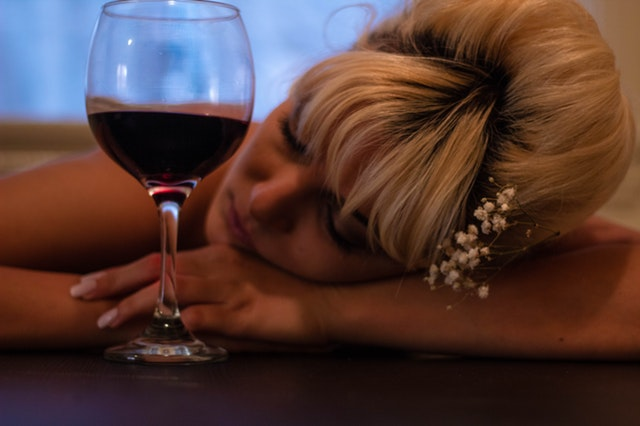 woman passed out holding glass of wine