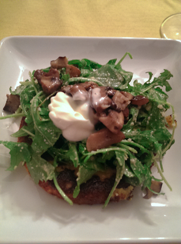 Polenta cake with warm mushroom salad topped with crème fraîche