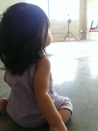 dressed in a cute purple romper, and waiting her turn behind the camera for the Paige Lauren baby photoshoot