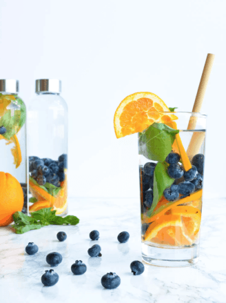Blueberry Orange Basil Detox Water is a refreshing way to stay hydrated this Summer. Check out this recipe and 16 other Flavored Water Recipes by clicking the link! | We Three Shanes