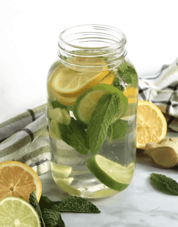 Flavored Water with Lemon, Mint, and Ginger is a refreshing way to stay hydrated this Summer. Check out this recipe and 16 other Flavored Water Recipes by clicking the link! | We Three Shanes