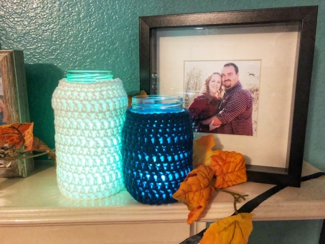 A large mason jar cover in a white crochet cozy sitting next to a blue crochet cozy on a smaller mason jar glowing from a candle inside the jars.