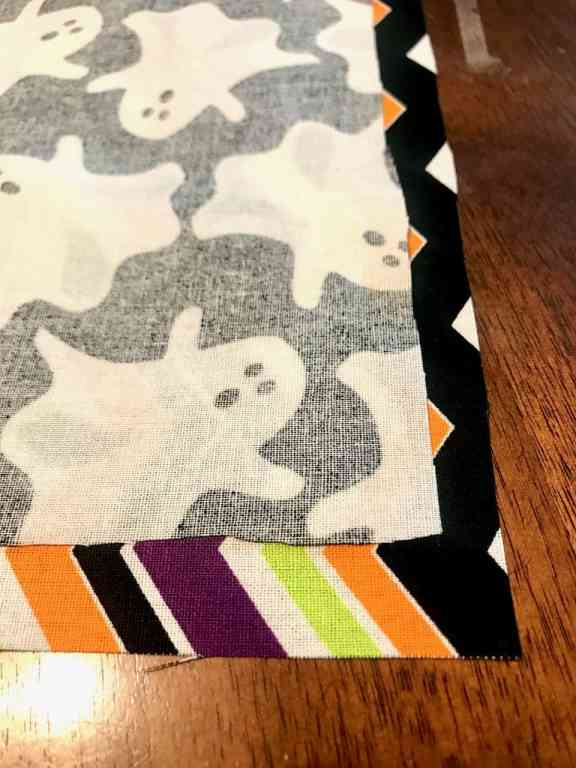 Add some holiday cheer to your dining room with a fun reversible table runner. This easy sew project uses fat quarters to create seasonal table decor that can be used for two holidays. | We Three Shanes