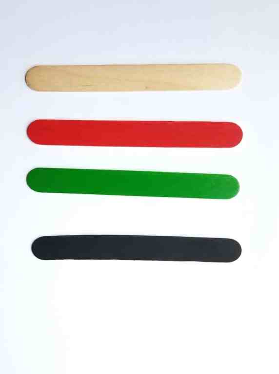 4 popsicle sticks line up one above the other.  The first is neutral. The next is painted bright red, then bright green, and the last one is black.