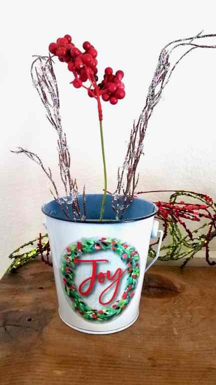 Christmas bucket with floral foam. Two glittery sticks are on each side and red berries are in the middle.