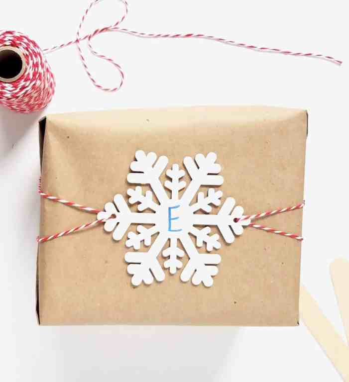 A box wrapped in brown paper with a snowflake gift tag sitting on top being held on by red and white bakers twine.