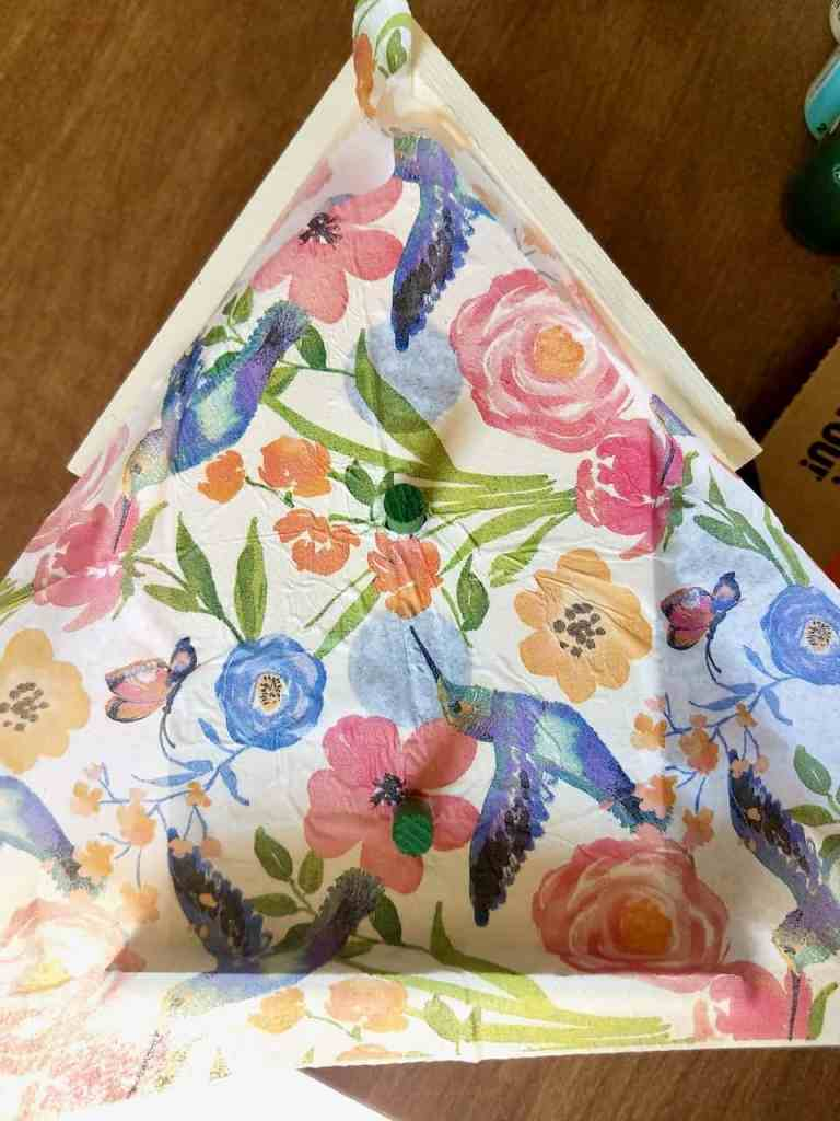 The garden theme napkin is slid on top of the mod podged birdhouse with the perches sticking up through the napkin.