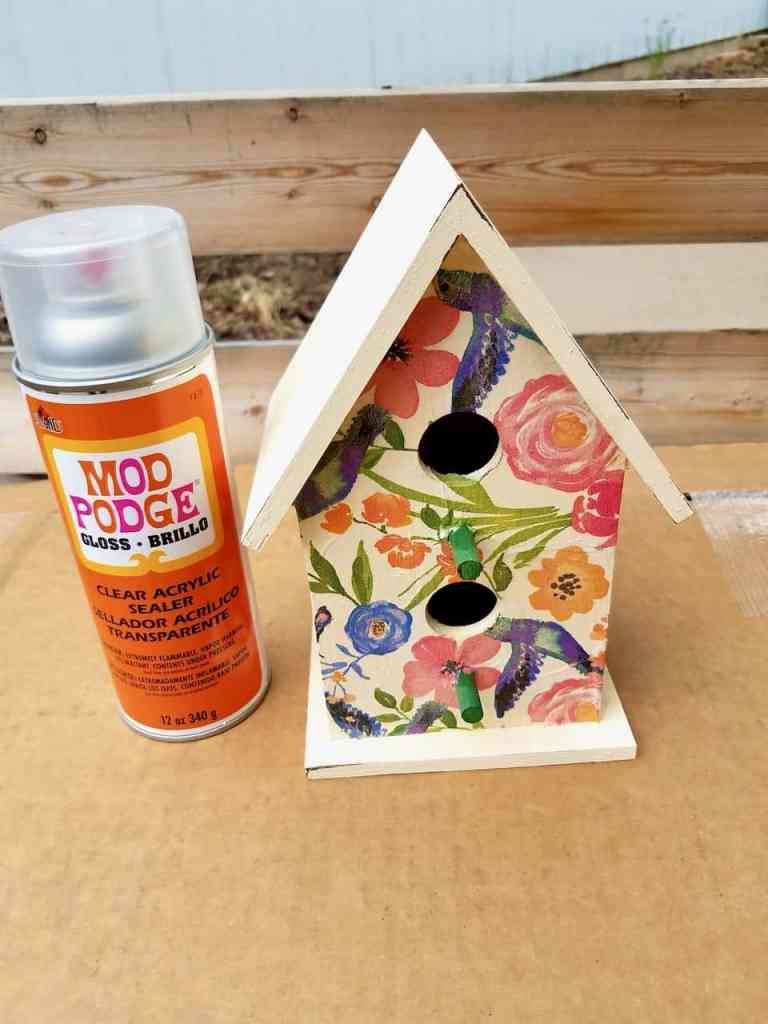 The finished decoupage and painted birdhouse outside and a can of Mod Podge brand clear acrylic sealer standing next to it.