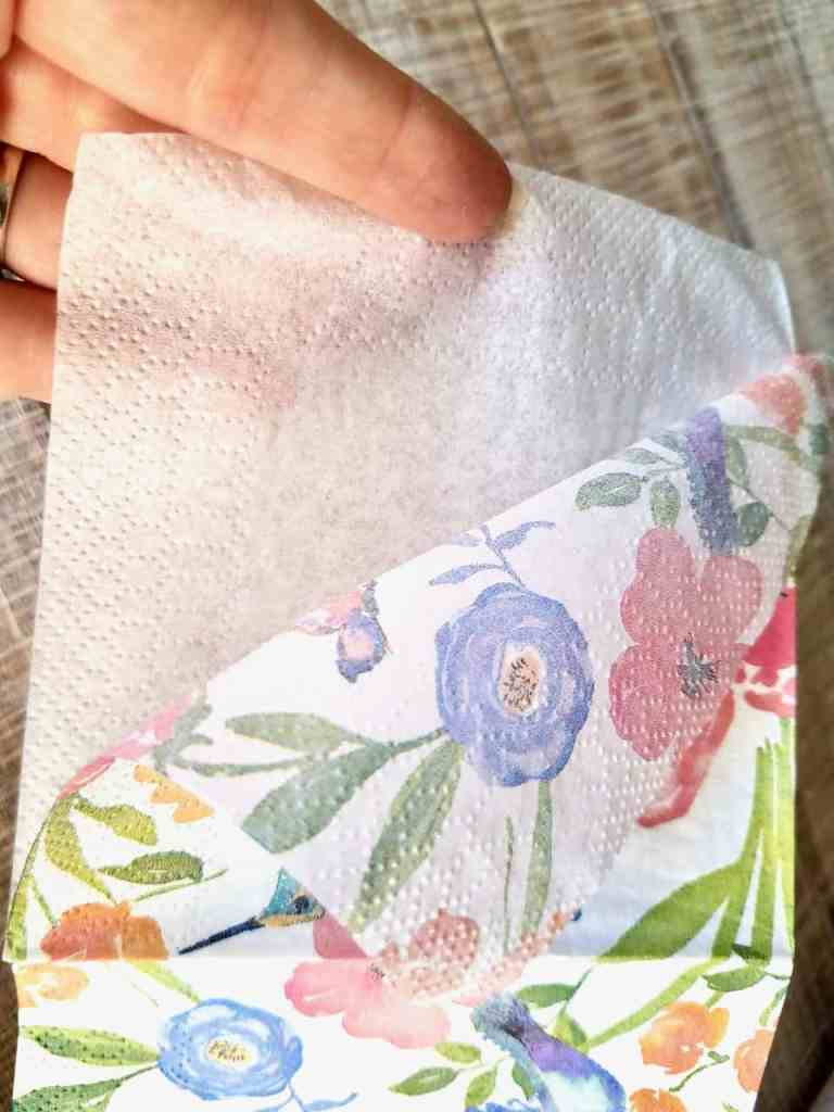 Finger's are pulling the layers of the napkin apart so you're left with one layer of napkin to decoupage with.