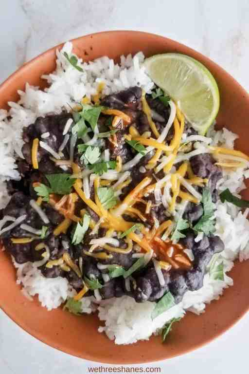 Burt orange bowl full of white rice topped with black beans, shredded cheese, chopped cilantro, a little red hot sauce with a lime wedge on the side sitting on a white counter top.