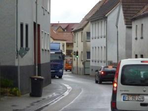 Mülltonnen, Asphalt und vor allem Autos prägen die Mitte unseres Dorfes. Von Aufenthaltsqualität ist hier keine Rede. Was machen wir bloß, wenn die Autos weg sind? Foto: Nissen