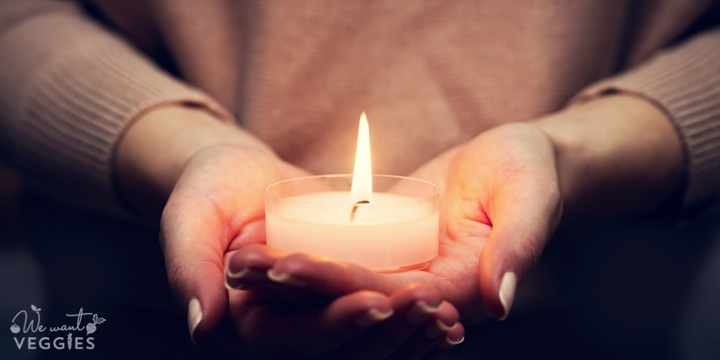 Candle light glowing in woman's hands.