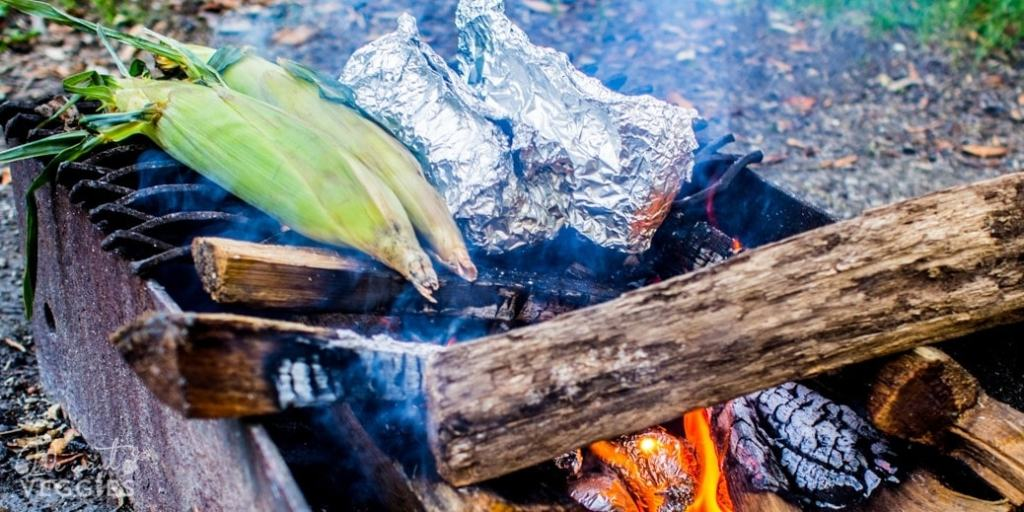 Campfire foil packets cooking with fresh sweet corn over indirect heat.