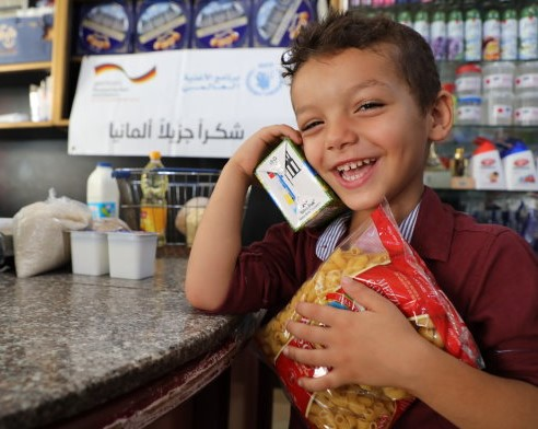 Photo: WFP/Khaled Abu Shaaban, a child in the Gaza Strip enjoying buying his favourite food at a local shop using WFP electronic voucher.