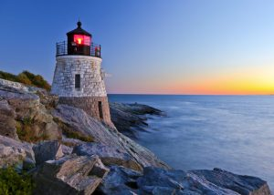 Beautiful lighthouse by the ocean at sunset.
