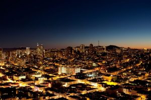 A view of a city at night with a sunset on the horizon - San Jose.