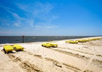 Gulf coast beach in Gulfport, Mississippi with lounge chairs along the shoreline.