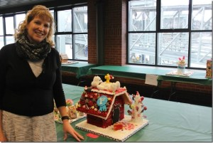Daniele O'Connell proudly displays her team's gingerbread house at the competition. Photo credit: Darcy Walters.