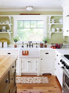 """""""Pine floors and a butcher block island kept costs down but deliver a charming, homey style that the clients are delighted with,"""" Jonathan says. """"The white farmhouse sink is clean and classic. You do not need an huge budget to have a kitchen alive with style."""" Photo courtesy: Jonathan O'Brien."""