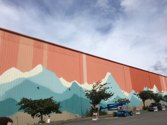Artists Gretchen Leggit and Max McNett used industrial paint sprayers and exterior paint to build the base layers of the mural. Photo courtesy: Nick Hartrich.