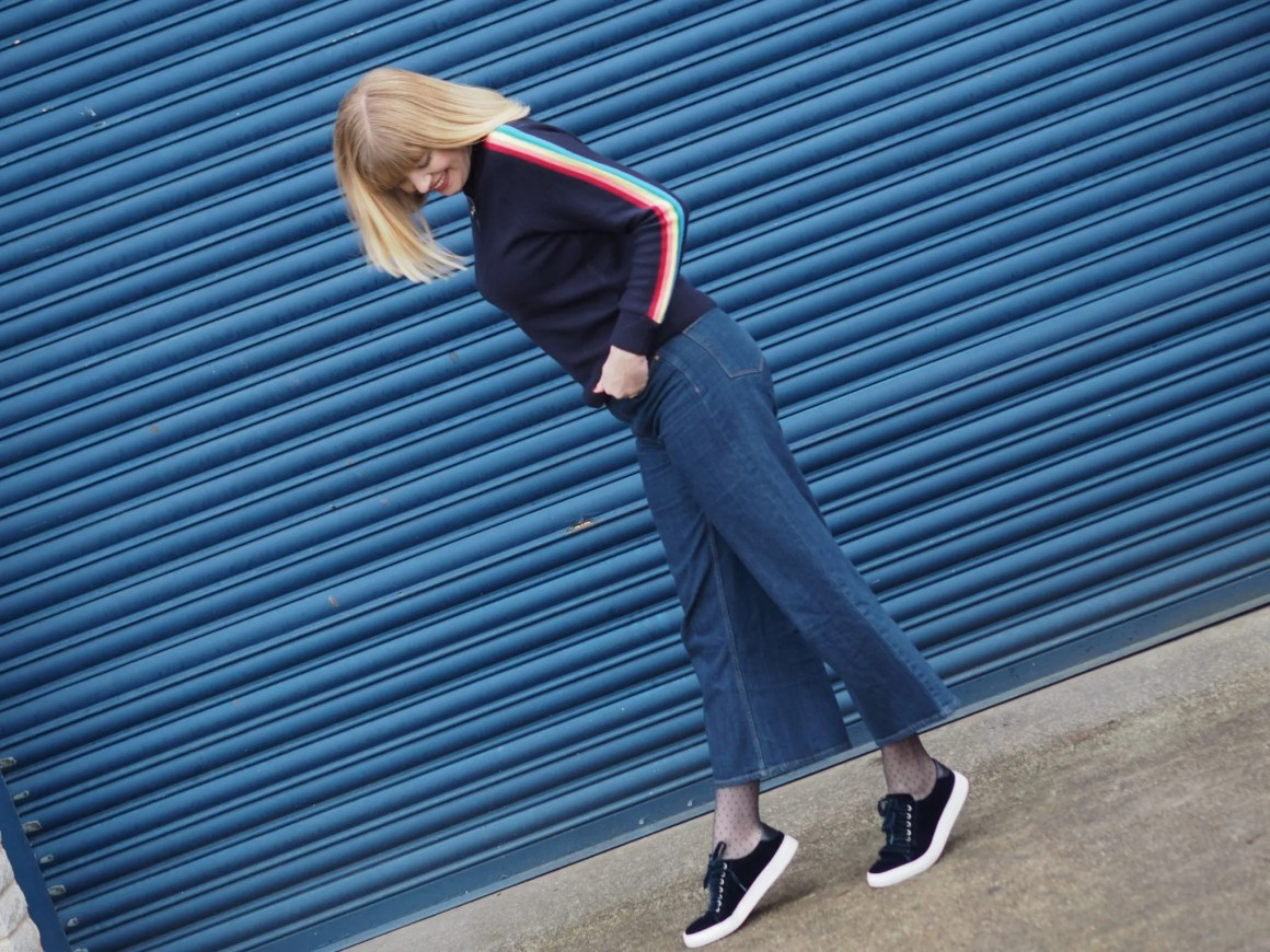 Forty plus blogger What Lizzy Loves wearinh rainbow sleeve sweater and wide leg jeans with velvet trainers